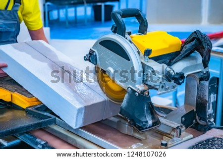 A man sawing concrete. Construction works. Cutting saw. Worker sawing stone cutting saw. Saw with a diamond disc. Cutting stone saw. #1248107026