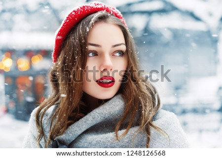 Outdoor close up portrait of young beautiful fashionable woman with red lips,  wearing woolen beret, scarf, posing in street of european city. Winter fashion, Christmas holidays concept. Copy space #1248126568