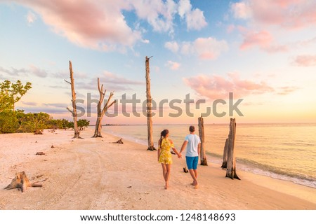 Couple walking on beach at sunset romantic travel getaway, idyllic Florida destination, Lovers key beach state park in the gulf of Mexico. Woman and man holding hands relaxing. Southwest Florida. #1248148693