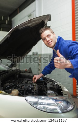 Portrait of auto mechanic gesturing thumbs up as he checks oil level of car #124821157