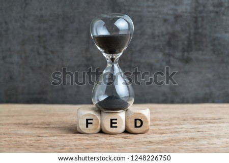 Federal Reserve, FED target and speed to raise interest rate concept, hourglass or sandglass on cube wooden block with alphabet building acronym FED on wooden table with dark background. #1248226750