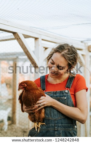 Happy young woman with a brown hen #1248242848