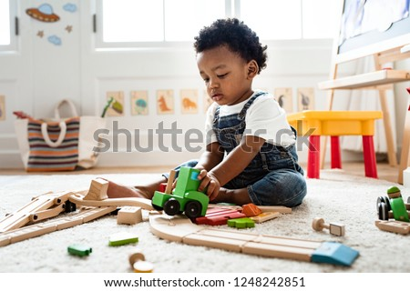 Cute little boy playing with a railroad train toy Royalty-Free Stock Photo #1248242851