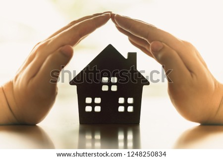 Hands of a young woman surround a wood house model. Real estate agent offer house, property insurance and security, affordable housing concepts #1248250834