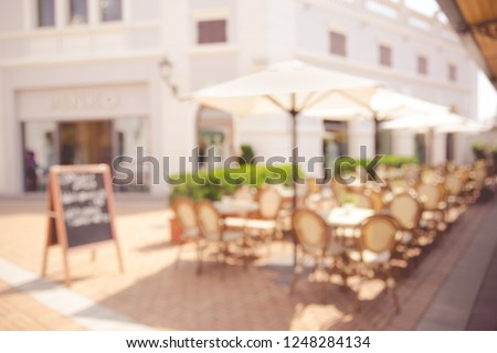 Blurred abstract background of outdoor cafe in Milan, Italy. Outdoor cafe with tables, chairs at the old town. #1248284134