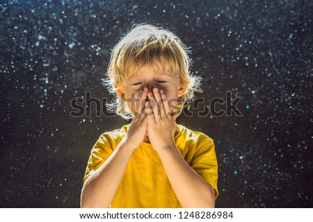 Allergy to dust. Boy sneezes because he is allergic to dust. Dust flies in the air backlit by light #1248286984