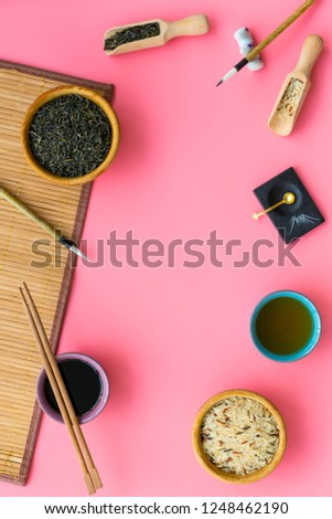 Chinese traditional symbols concept. Tea, rice, hieroglyph love, bamboo table mat, chopsticks, soy sause on pink background top view frame space for text #1248462190