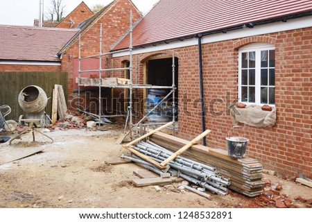 Building site in UK with brick house extension under construction Royalty-Free Stock Photo #1248532891