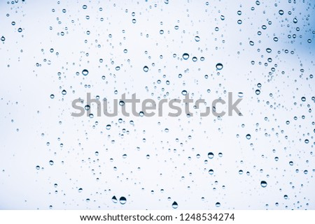 Dirty window glass with drops of rain. Atmospheric blue light background with raindrops. Droplets and stains close up. Detailed transparent texture in macro with copy space. Rainy weather. #1248534274