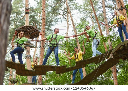 Group helps with climbing in high wire garden as a team training activity #1248546067