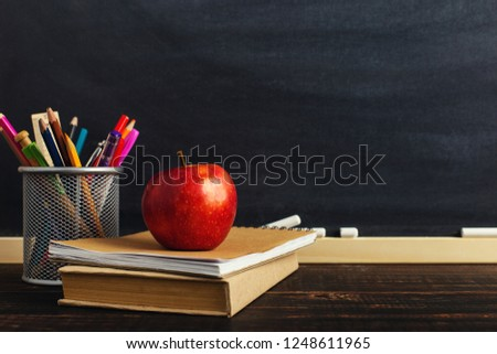 Teacher's desk with writing materials, a book and an apple, a blank for text or a background for a school theme. Copy space.