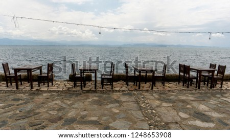 empty tables and chairs on the shore #1248653908