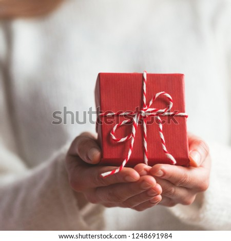 Hands with a gift wrapped in red paper and red bow. Close up. #1248691984