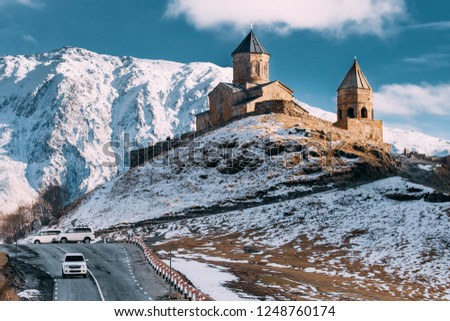 Stepantsminda, Gergeti, Georgia. Famous Gergeti Trinity Tsminda Sameba Church In Early Winter Landscape. Suv Moving Near Church In Beautiful Georgian Landscape In Early Winter #1248760174