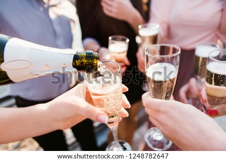 a young company pouring champagne into the wineglasses. young guys drink champagne at sunset. sparkling champagne in glass goblets. splashes of champagne #1248782647