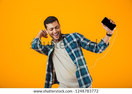 Excited young man wearing plaid shirt standing isolated over orange background, listening to music with earphones and mobile phone