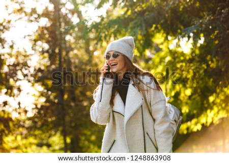Beautiful young woman dressed in autumn coat and hat walking outdoors, talking on mobile phone, laughing #1248863908