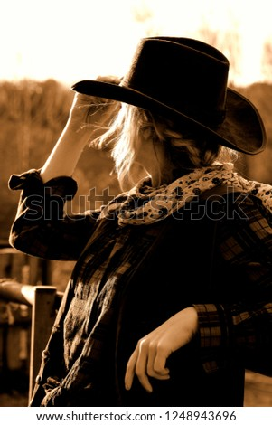 the singing blonde cowgirl on a windy sunset evening with her cowboy hat