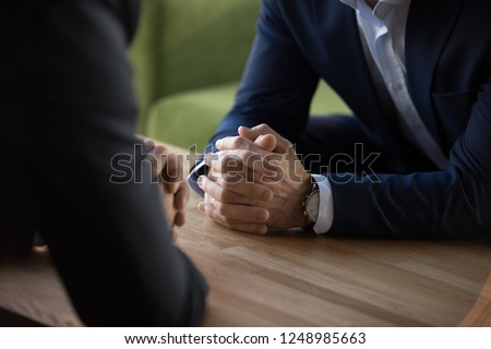 Purposeful confident restrained businessmen in suits sit at table opposite each other, close up male clenched hands in lock at desk. Complexity of decision self-control in stressful situation concept #1248985663