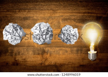 Glowing glass light bulb on wooden background #1248996019