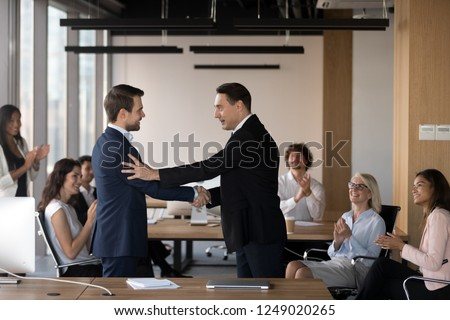 Mature director company owner congratulating young specialist handshaking standing at coworking area, diverse multiracial coworkers different colleagues applauding rejoicing for success of colleague #1249020265
