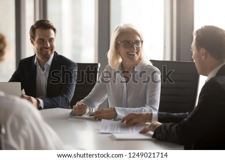 Happy successful well-dressed company members headed by aged woman in eyeglasses gathered together in boardroom at briefing. Business partners solve current matters negotiating sitting at office desk #1249021714