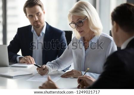 Businessmen sitting at desk headed by middle aged serious concentrated female in eyeglasses checking agreement document before signing it. Financial director ready affirm official paper with signature #1249021717