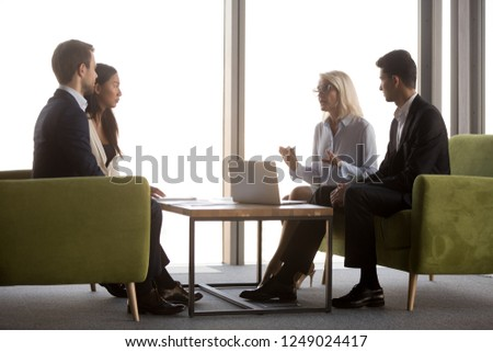 Side view diverse businesspeople negotiating sitting near panoramic window on couch in modern cozy office. Middle aged ceo talking with asian caucasian and middle eastern ethnicity partners or interns #1249024417