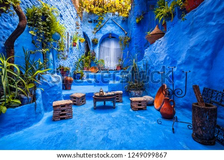 Typical moroccan courtyard in Chefchaouen blue city medina in Morocco with blue walls and decorated with various objects (pots, jugs)  #1249099867