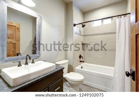 White and fresh bathroom interior with a rectangular vessel sink and ivory subway tile shower surround . #1249102075