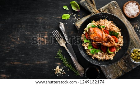 Baked quail with oatmeal and vegetables. On a black background. Top view. Free space for your text. #1249132174