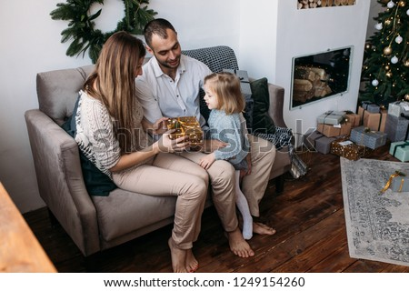 Parents and their  little child having fun indoors. Loving family with presents in room. Merry Christmas and Happy Holidays!  #1249154260