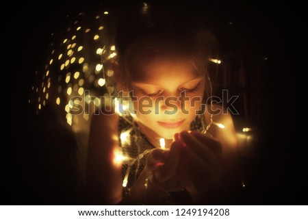 Cute little girl holds bright christmas garland in open hand. Christmas portrait, cozy style.  #1249194208