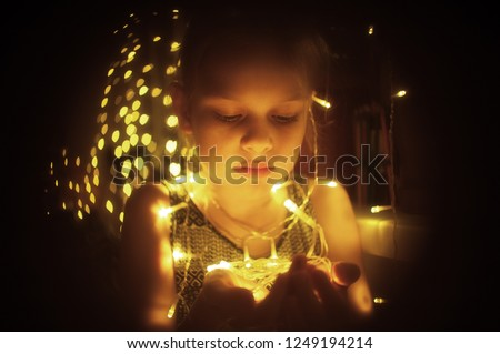 Cute little girl holds bright christmas garland in open hand. Christmas portrait, cozy style.  #1249194214