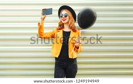 happy smiling woman taking selfie picture by smartphone holding black helium air balloon in round hat, yellow jacket on metal wall background