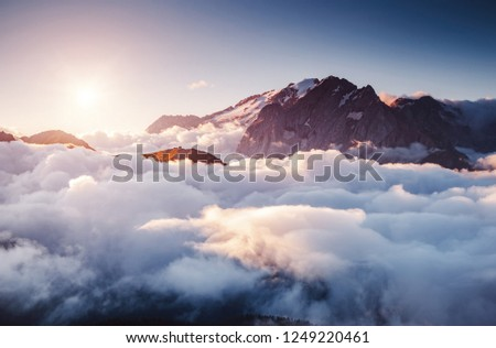 Thick fog covered the ridge in morning. Location place Val di Fassa valley. Scenic image of famous glacier Marmolada, passo Sella, Dolomiti, South Tyrol, Italy, Europe. Explore the beauty of world. #1249220461