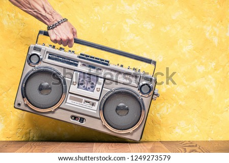 Retro outdated portable stereo boombox radio receiver with cassette recorder from circa 1980s in a strong man's hand front concrete textured yellow wall background. Vintage old style filtered photo  #1249273579