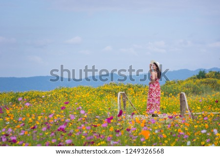 Beautiful woman in nature flower, Her wear white dresses and red hat in Tung Bua Tong Mexican sunflower field in Mae Moh Coal Mine, Lampang Province, Thailand. #1249326568
