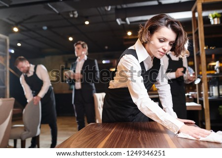 Serious busy young waitress and her colleagues preparing restaurant for open and making cleanup: she wiping wooden table with cloth #1249346251