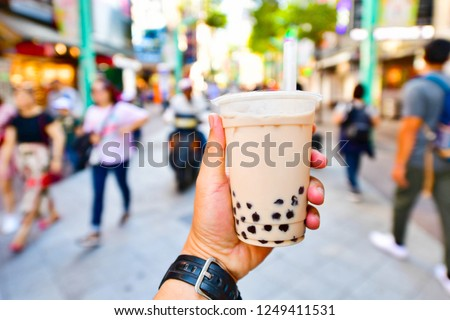 Hand holding a plastic glass of Taiwan iced bubble milk tea on crowded street background.Bubble milk tea is a very popular drinks in Taipei, Taiwan. #1249411531