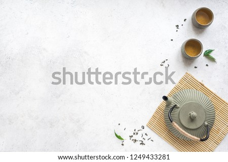 Asian Tea Set -  iron teapot and ceramic teacups with green tea and leaves. Traditional tea composition on white background, copy space. #1249433281