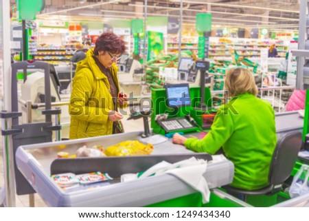 Russia, Samara, November 2018: beautiful mature women pay for goods with a bank card. #1249434340
