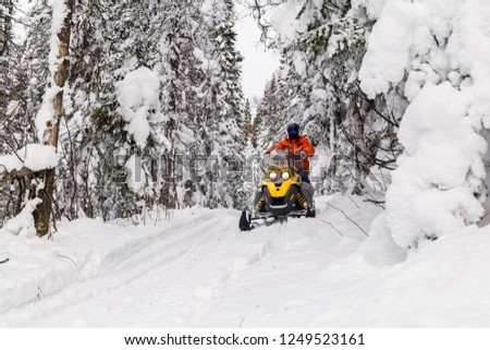 Athlete on a snowmobile moving in the winter forest in the mountains of the Southern Urals. #1249523161