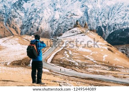 Stepantsminda, Gergeti, Georgia. Man Tourist Backpacker Traveler Photographer Taking Pictures Photos Of Holy Trinity Church - Tsminda Sameba.  Beautiful Georgian Landscape In Early Winter.