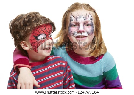 Young boy and girl with face painting of cat and spiderman smiling on white background
