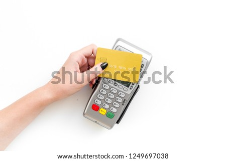 Pay by payment terminal. Paypass  technology. Woman's hand hold credit card, bring card to terminal  on white background top view copy space #1249697038