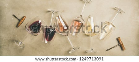 Flat-lay of red, rose and white wine in glasses and corkscrews over grey concrete background, top view, wide composition. Wine bar, winery, wine degustation concept #1249713091