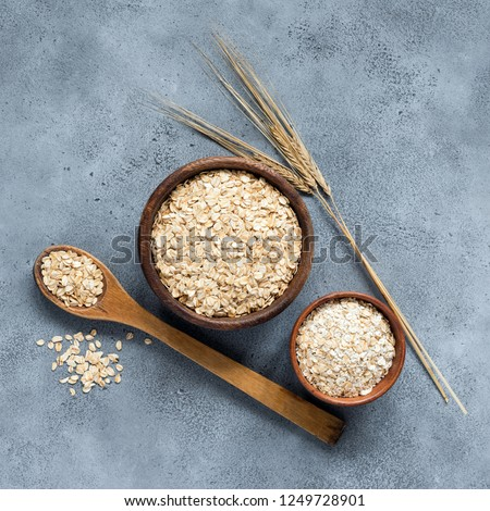 Rolled oats or oat flakes in wooden bowl on concrete background, top view. Nutrition, dieting, healthy eating concept. Square crop #1249728901
