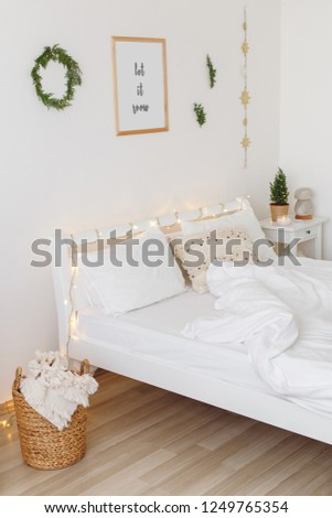 Christmas or new year winter home interior decor. Holiday decorated room: little christmas tree in a pot, coniferous twigs, pine branches, led garland lights. White stylish cozy scandinavian bedroom. #1249765354