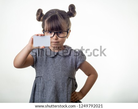 Smart or clever child holding discount bank card in her hands. Kid with credit card. Little girl with glasses showing empty blank paper note copy space.